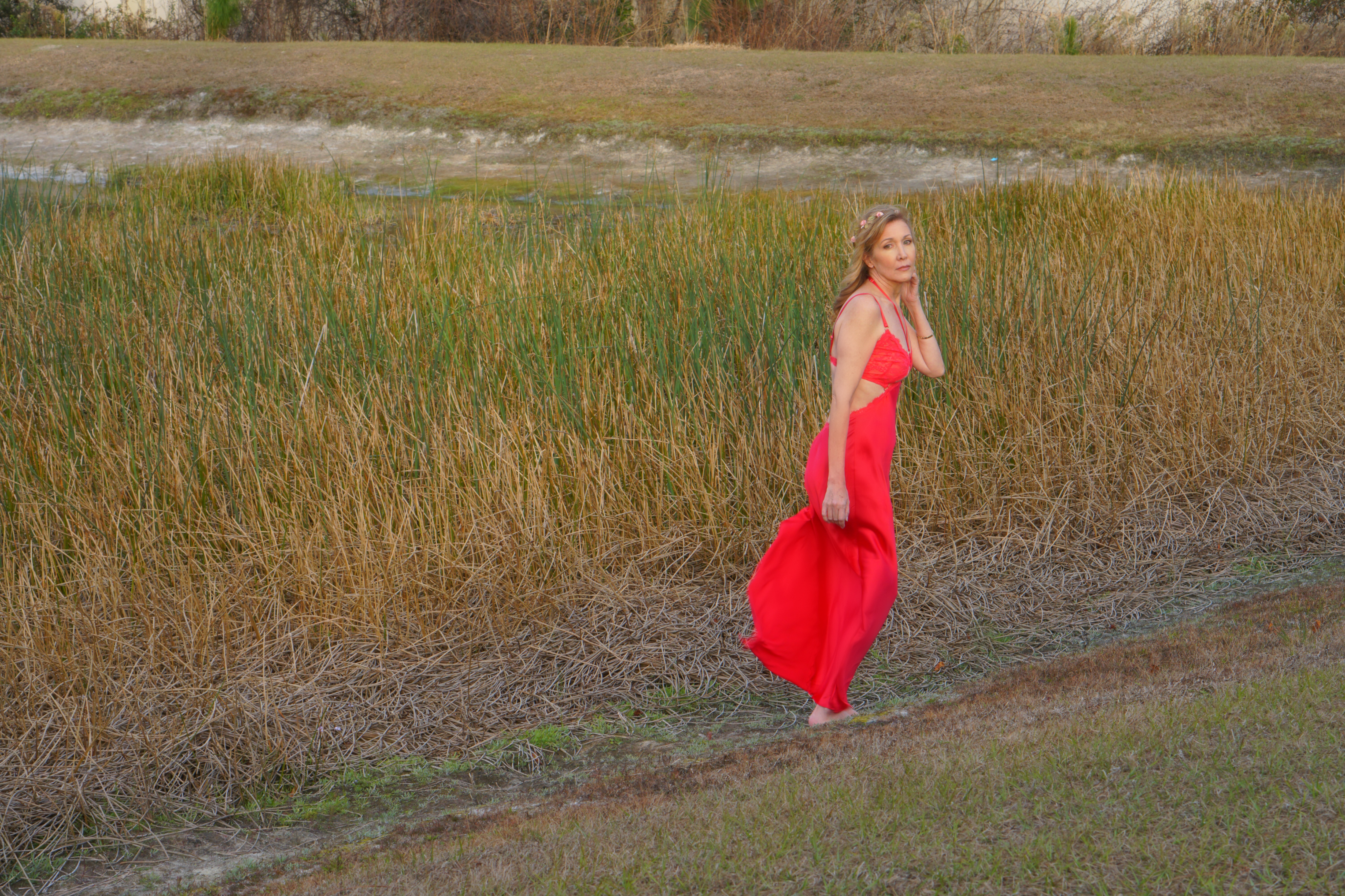 Nina Bandoni sharing a journey wearing red dress beside the grass
