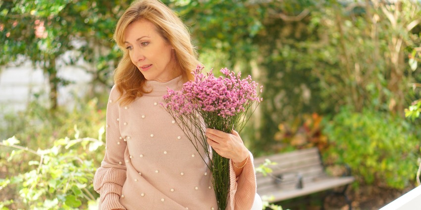 Nina from Sharing A Journey Wearing Pink Sweater with pearls and bell sleeves