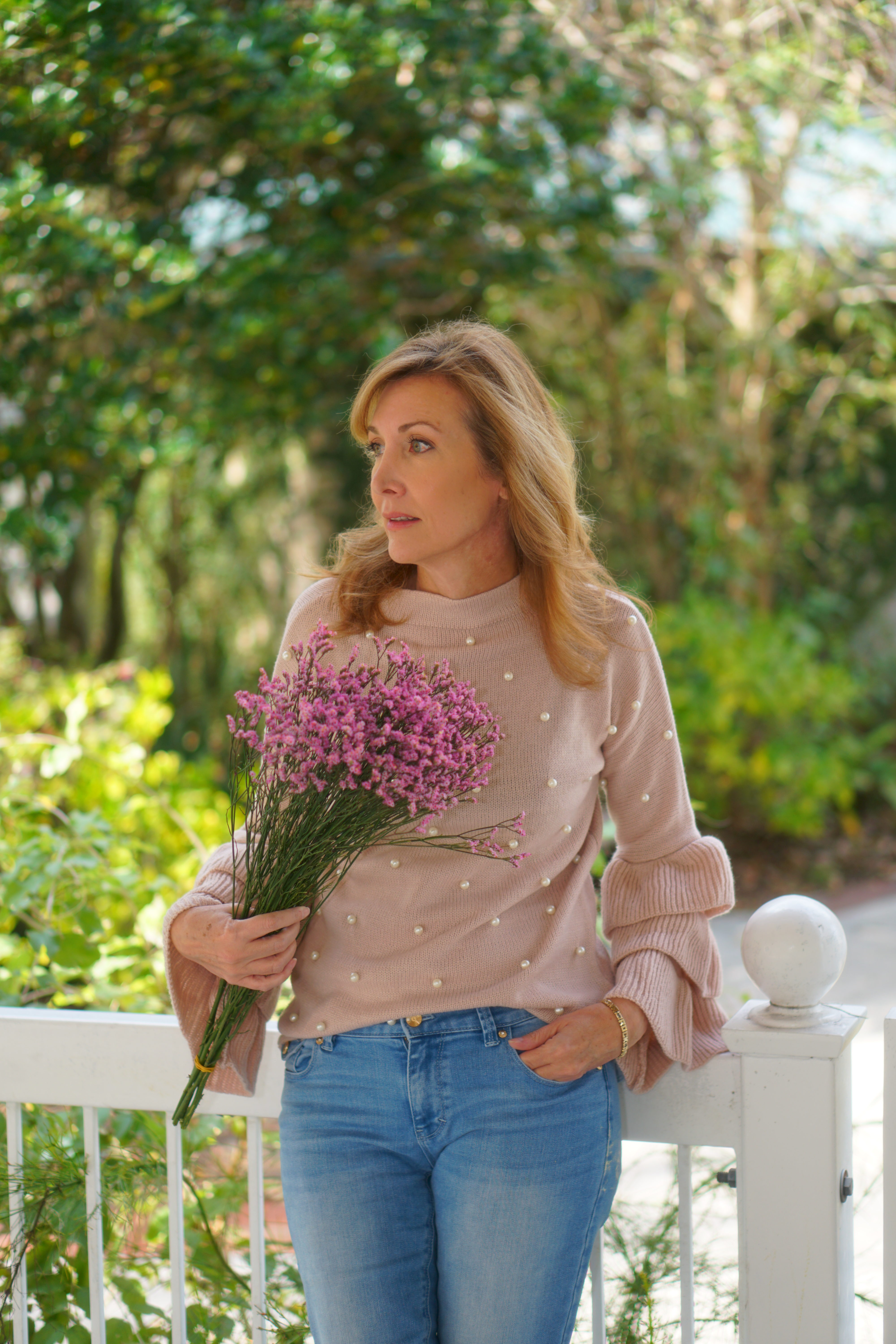 Nina Bandoni of Sharing A Journey with purple flowers wearing pink sweater and blue jeans