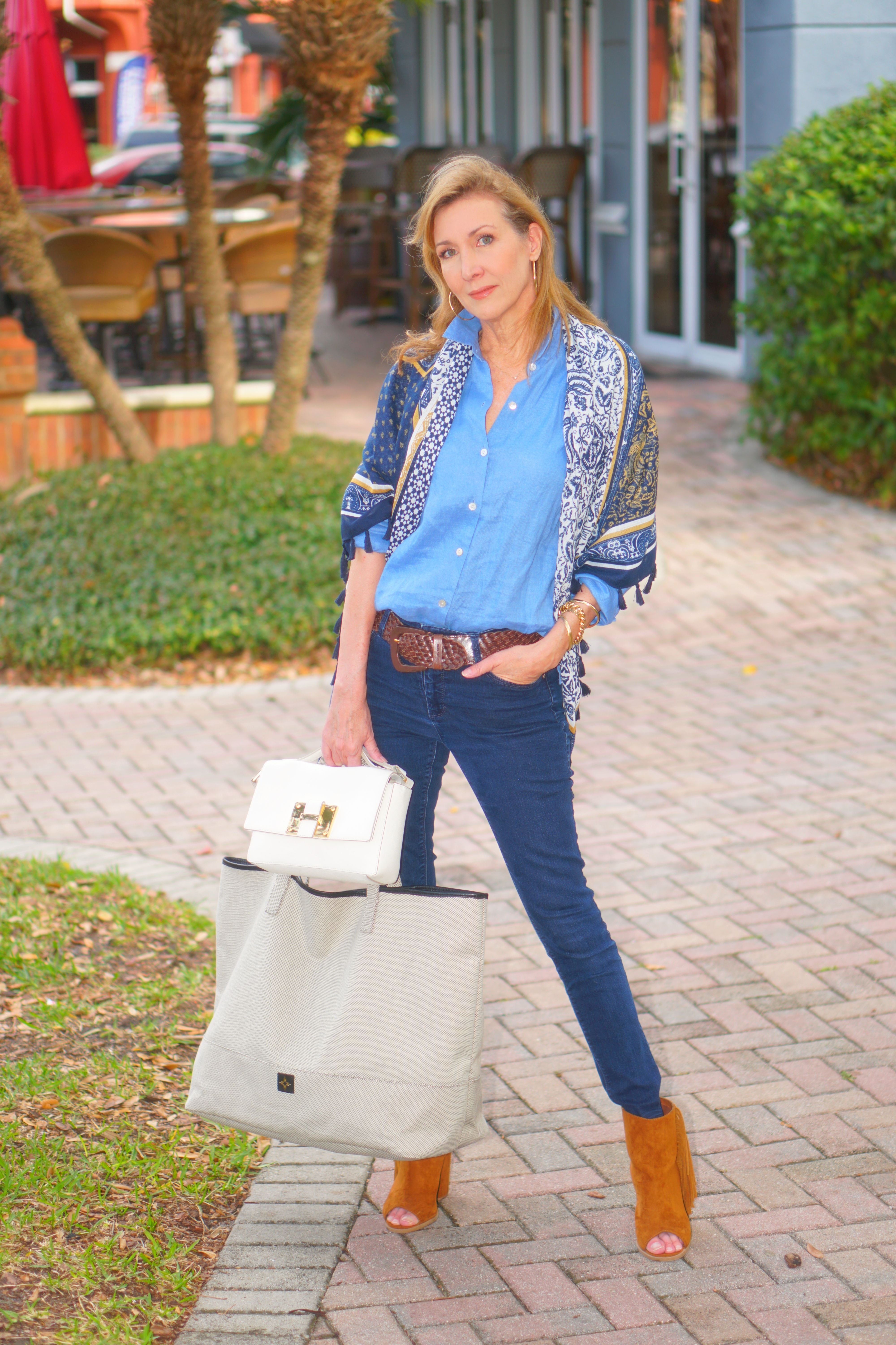 Woman in blue jeans and blue top carrying a bag