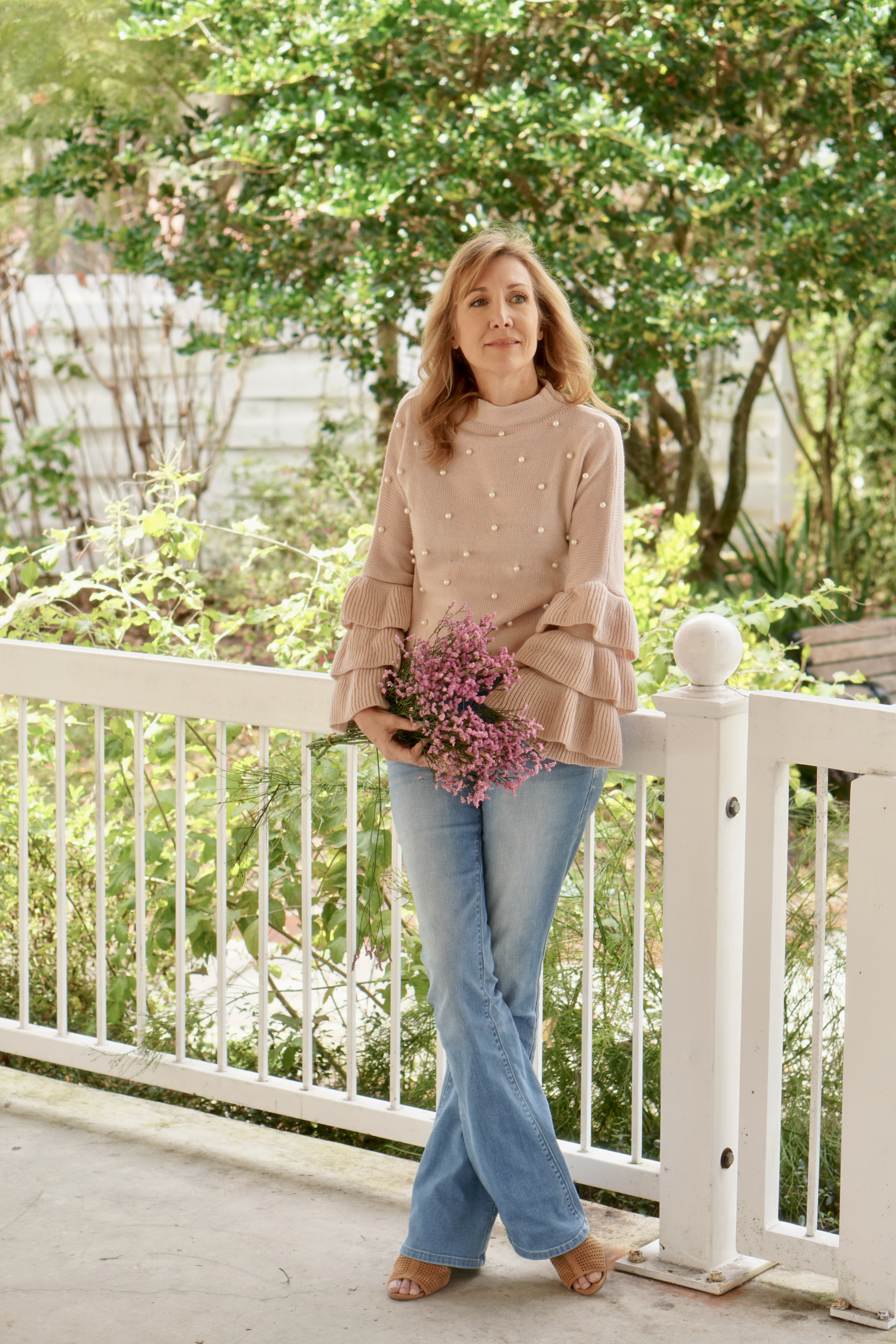 Nina Bandoni Sharing A Journey wearing pink sweater and blue jeans